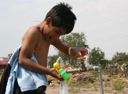 Un niño juega con una pistola de agua en el cementerio de Xicohtzinco, donde han enterrado a la maestra que murió de influenza.