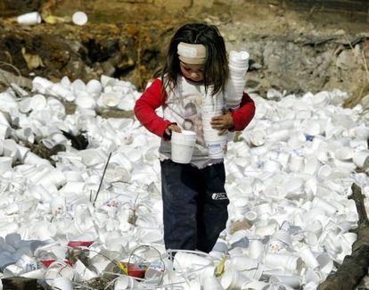 Una niña recoge vasos de plástico en un vertedero.