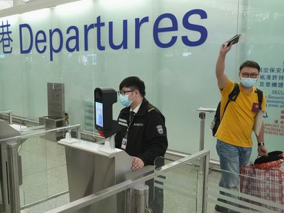 Un hombre se despide antes de embarcar en el aeropuerto de Hong Kong para trasladarse de manera definitiva al Reino Unido este miércoles