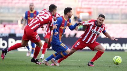Messi trata de regatear a Mario Hermoso (izquierda) y Koke este sábado en el Camp Nou.