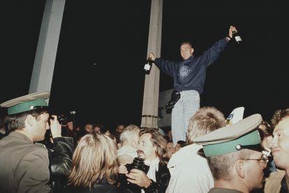 Un joven celebra la caída del muro de Berlín en Checkpoint Charlie, el 9 de noviembre de 1989.
