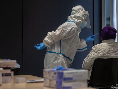 Una persona recibe una prueba PCR en un dispositivo de cribados masivos en el barrio del Raval, en Barcelona.