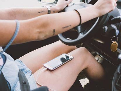 Una chica conduce con el móvil en las piernas.