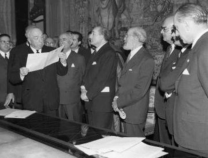 Representantes de la Fundación Juan March, la Biblioteca Nacional, el Gobierno y Ramón Menéndez Pidal (cuarto por la derecha), en el acto de entrega del códice del Cantar de Mío Cid, el 20 de diciembre de 1960. Abajo, la portada y los primeros versos del manuscrito.