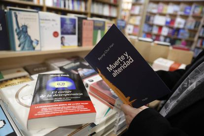 Un hombre toma un libro de filosofía en la la librería Antonio Machado de Madrid.