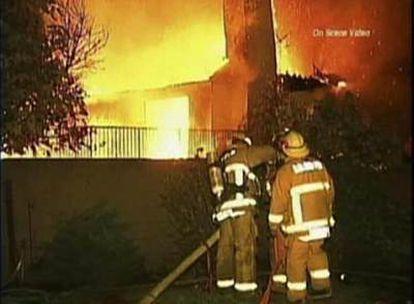 Los bomberos combaten el fuego en la casa donde se produjo la matanza.