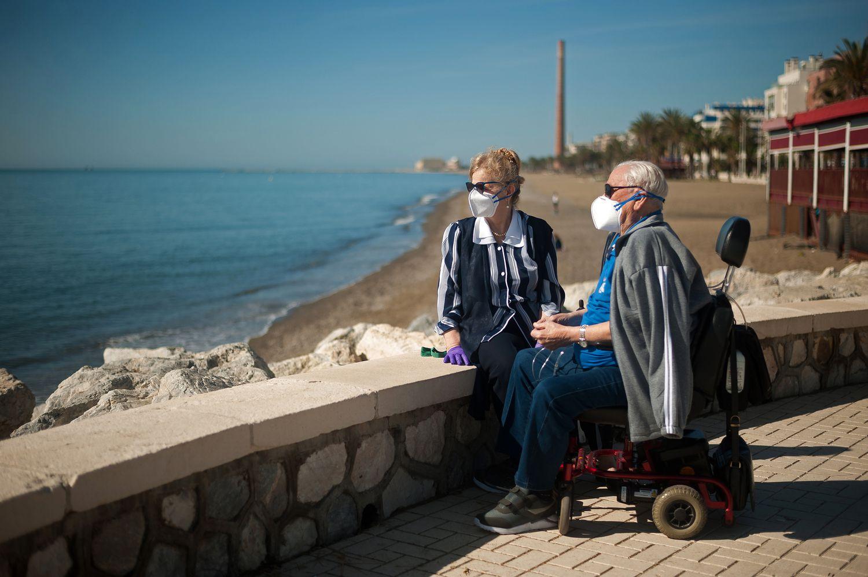 Una pareja de pensionistas descansa en el paseo marítimo de una playa malagueña.