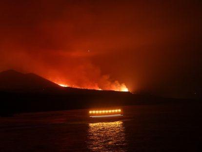 Los guardacostas pasan mientras la lava llega al mar, en una imagen tomada desde el puerto de Tazacorte.