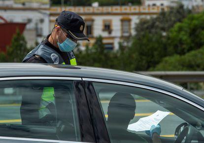 Un agente de la Policía Nacional durante un dispositivo de control de tráfico en la salida de Sevilla a Huelva para evitar desplazamientos innecesarios con motivo del puente de mayo.