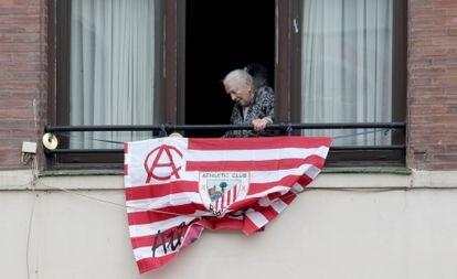Una mujer junto a una bandera del Athletic antes de las últimas finales de Copa.