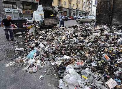 Dos trabajadores recogen basura ayer en una calle de Nápoles.