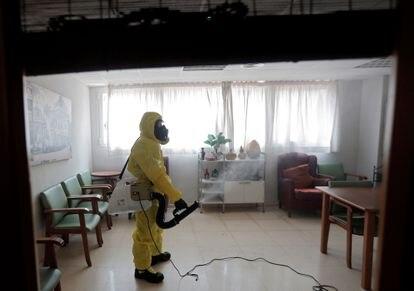 Un miembro de la Unidad Militar de Emergencias desinfecta una residencia de mayores en Valencia.