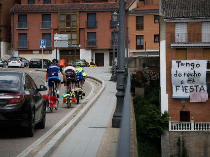 Un grupo de ciclistas atraviesa el puente de entrada a Tordesillas, que cruza el río Duero, donde lleva meses colgado un cartel en defensa del Toro de la Vega.