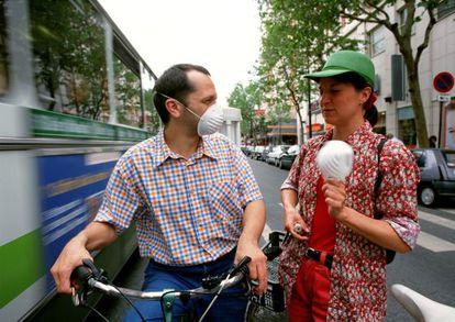 Dos ciclistas con  mascarilla por las calles de París. / France Press