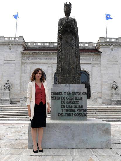 La presidenta de la Comunidad de Madrid, Isabel Díaz Ayuso, posa junto a una estatua de la reina Isabel I de Castilla, frente a la sede de la Organización de Estados Americanos (OEA), en Washington (Estados Unidos).