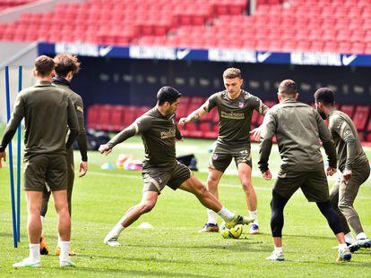 Trippier (en el centro) junto a Luis Suárez y demás compañeros en el entrenamiento del Atlético del viernes.