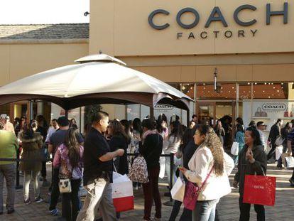 Compradores haciendo cola para entrar a la tienda Coach Factory.