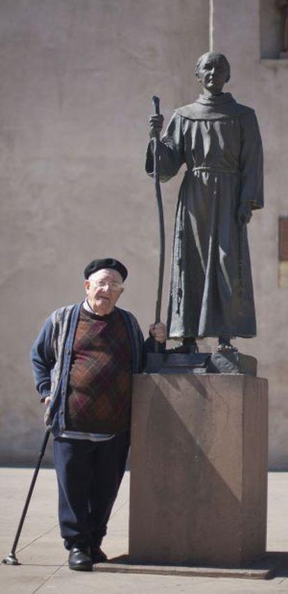 El padre Teodomiro Fuentes, junto a una estatua de Junípero Serra en la misión de San Gabriel, en Los Ángeles.