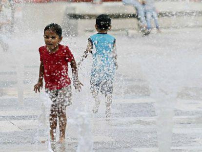 Una niña y un niño juegan con una fuente de agua en San José (Costa Rica).
