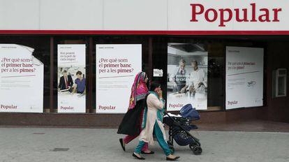 Unas mujeres pasan por delante de una oficina del Banco Popular, en Barcelona.