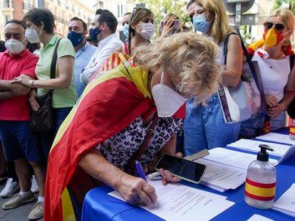 Una mujer firma contra los indultos en la manifestación de la plaza de Colón de Madrid el pasado domingo.