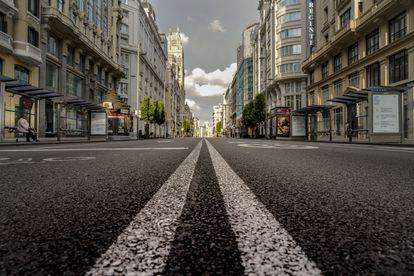 La ciudad como nunca la habíamos visto. Una mujer espera al autobús en una solitaria Gran Vía, una de las principales arterias de Madrid y convertida, con su silencio, en uno de los iconos del Madrid del confinamiento.