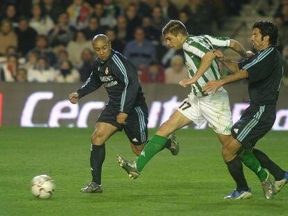 Joaquín dispara entre Roberto Carlos y Figo en el Betis-Real Madrid de enero de 2004 (1-1).