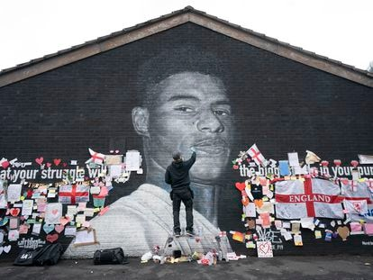 El grafitero Akse P19 repara el mural dedicado en Manchester al futbolista Marcus Rashford, después de que fuera dañado tras su fallo en los penaltis de la Eurocopa.