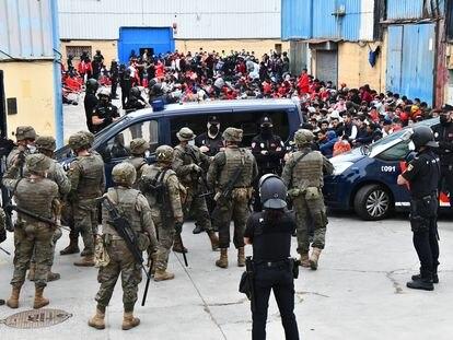 Agentes de la Policía Nacional y miembros del Ejército custodian a los inmigrantes que están en las naves del Tarajal, el martes.