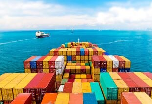 Horizontal wide angle view of heavy loaded container cargo ship in busy strait of Malacca.