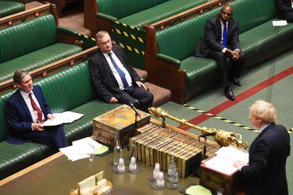 Keir Starmer escucha sentado este miércoles la réplica de Boris Johson en una Cámara de los Comunes casi vacía.