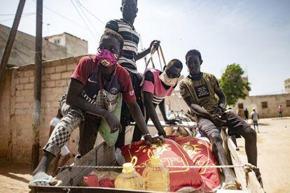 Una familia se lleva productos de primera necesidad durante el reparto de comida puesto en marcha por el Gobierno senegalés, el pasado martes en Dakar.