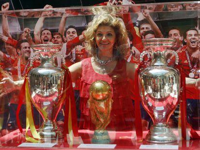 Una aficionada posa con los tres títulos logrados por España desde 2008.