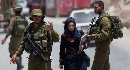 Una mujer palestina pasa junto a soldados israelíes en Hebrón.