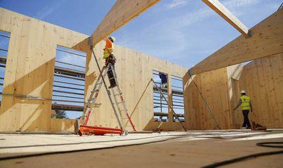 Dos operarios montan láminas de madera en unas viviendas de Hondarribia (Gipuzkoa).