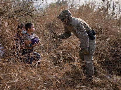 Un policía texano conversa con una solicitante de asilo hondureña y su hijo de 4 años después de que estos cruzaran el Río Bravo el 9 de marzo en Peñitas, en el Valle del Río Grande.
