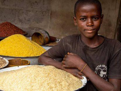 Un niño junto a una bandeja de arroz en su tienda en el mercado de Ajara en Badagry, cerca de Lagos, en Nigeria.