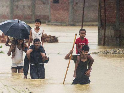 Varios nepalíes huyen de sus casas inundadas en Ramgadhwa, en Nepal, este domingo.