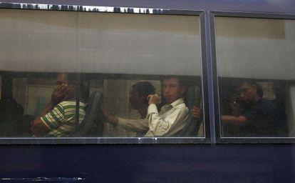 Inmigrantes en un autobús policial, el día 5 en Atenas.