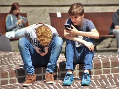 Dos adolescentes miran su móvil antes de entrar a clase.