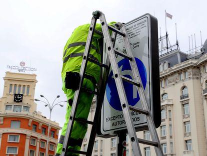 Dos operarios cambian las señales de Madrid Central en la Plaza de Cánovas del Castillo, este miércoles.