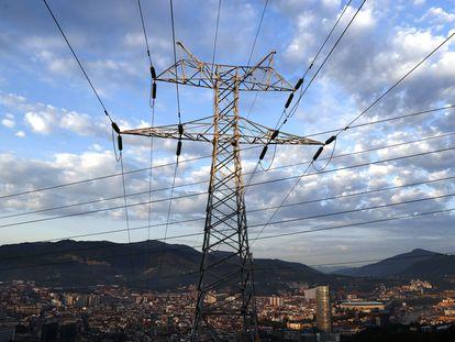 Una torre de transporte de energía perteneciente a red eléctrica, con Bilbao al fondo.