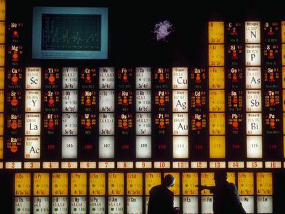 Dos científicos usan una tabla periódica para hablar sobre el elemento holmio en el Lawrence Hall of Science de la Universidad de California en Berkeley en una imagen retrospectiva.