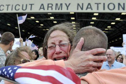 Una madre abraza a su hijo a su llegada a la base aérea de Connecticut.