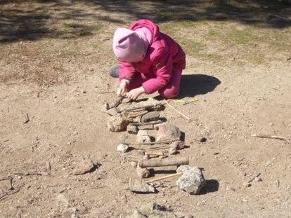 Una alumna del Grupo de Juego en la Naturaleza Saltamontes, de Collado Mediano, crea un puente con palos y piedras en su escuela en la naturaleza.