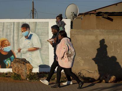 Una familia pasa junto a un mural que promueve la vacunación contra la covid-19 en Duduza, al este de Johannesburgo, Sudáfrica, en junio de 2021.