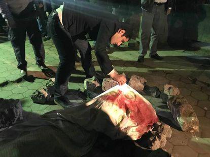Un persona inspecciona el cadáver de una de las víctimas del atentado suicida de este lunes en El Cairo.