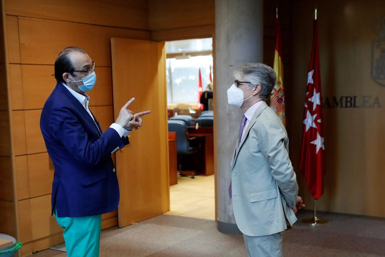El diputado socialista y presidente de la Comisión de Reconstrucción, Carlos Carnero (d) conversa con el diputado de Vox, José Ignacio Arias (i) durante la constitución de la comisión en la Asamblea de Madrid este miércoles.
