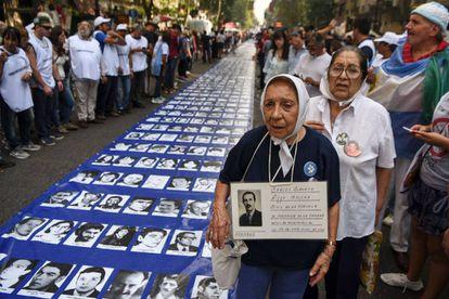Madres de Plaza de Mayo junto a fotografías de desaparecidos en la dictadura argentina.