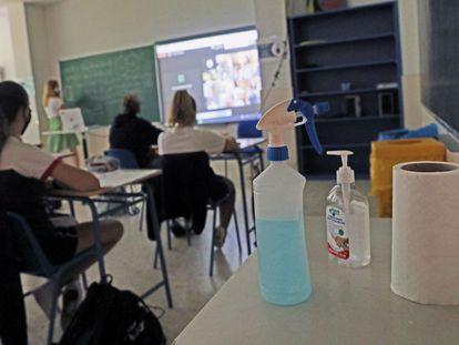 Productos desinfectantes colocados en los pupitres desde donde los alumnos atienden a las clases semipresenciales impartidas en un colegio de Madrid.